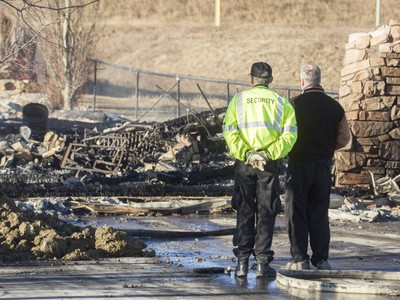 A homeowner stands looking at the remains of his house on Kincora Drive N.W. on Tuesday morning after a major fire.