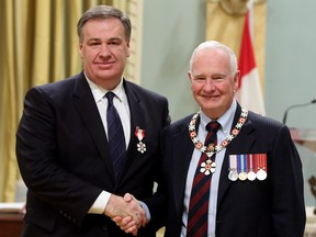 Murray Edwards, left, made a member of the Order of Canada by Gov. Gen. David Johnston in 2014, is a resident of London, U.K., according to a new regulatory filing by Canadian Natural Resources.