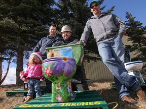 Left to Right: Kevin Gelinas - with daughter Paisley - Sean Pitt and Mike Hewitt with toilets they decorated for the Game of Thrones Fundraiser for the Enbridge Ride to Conquer Cancer in Calgary, Ab., on Thursday March 17, 2016. Mike Drew/Postmedia