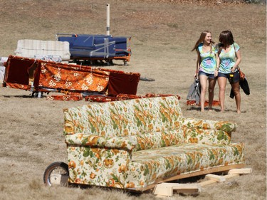 2010: Ashley Stenning (left) and Lane Millar walk through the destroyed couches that were used in a couch race during the annual Bermuda Shorts day.