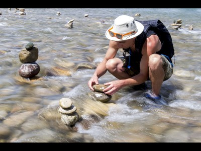A young man who would only be identified as 'Show Biz' tediously builds cairns, or 'living rocks', in the Bow River at Prince's Island Park in downtown Calgary, Alta., on Wednesday, May 18, 2016. Show Biz says his cairns serve a variety of artistic, therapeutic and calming purposes, his favourite of which is creating a sense of welcomeness and community in an area too often hit with petty crime. Lyle Aspinall/Postmedia Network
