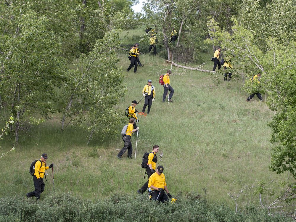 A Calgary Search and Rescue crew scours a heavily wooded hillside next to Memorial Drive, west of the Centre Street Bridge, in Calgary, Alta., on Wednesday, June 8, 2016. Police had found a dead person in the area that morning. Lyle Aspinall/Postmedia Network