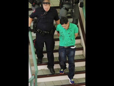 A blood covered man is escorted in handcuffs form a stabbing incident in the Perpetual Wellness Chinese Medicine Centre on Thursday June 16, 2016