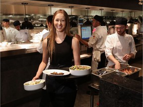 Servers work during the busy lunch hour at the Earls.67 restaurant in downtown Calgary on Monday July 11, 2016. Instead of the traditional tipping method the rebranded location is testing a new 16 percent hospitality charge to all bills. Gavin Young/Postmedia