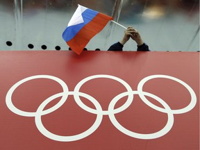 FILE - In this Feb. 18, 2014, file photo, a Russian skating fan holds the country's national flag over the Olympic rings before the start of the men's 10,000-meter speedskating race at Adler Arena Skating Center during the 2014 Winter Olympics in Sochi, Russia. On Monday, July 18, 2016 WADA investigator Richard McLaren confirmed claims of state-run doping in Russia.