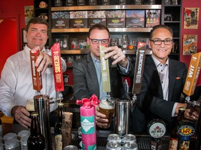 Alberta Minister of Agriculture and Forestry Oneil Carlier, left, Terry Rock, Alberta Small Brewers Association and  Minister of Finance and Treasury Board president Joe Ceci toast the new subsidies announced for small breweries at Village Brewery in Calgary, on Thursday, July 28, 2016.