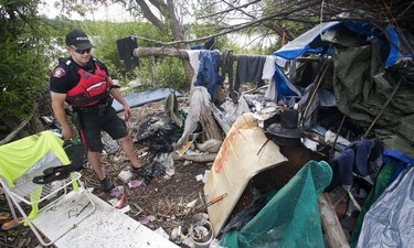 Calgary Police Marine Unit Constable Chris Terner walks through the squalor of an illegal encampment hidden from view in underbrush along the banks of the Bow River near Inglewood Golf Club Monday, Aug. 8, 2016.