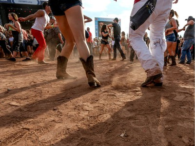 Dancers kick up the dust as Dustin Lynch performs at day 3 of Country Thunder at Prairie Winds Park in Calgary, Ab., on Sunday August 21, 2016. Mike Drew/Postmedia