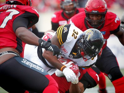 Hamilton Tiger-Cats C.J. Gable is brought down by the Calgary Stampeders during CFL football in Calgary, Alta., on Sunday, August 28, 2016. AL CHAREST/POSTMEDIA