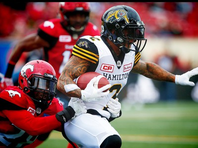 Hamilton Tiger-Cats Chad Owens avoids a tackle by Brandon Smith of the Calgary Stampeders during CFL football in Calgary, Alta., on Sunday, August 28, 2016. AL CHAREST/POSTMEDIA