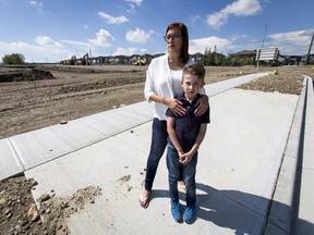 Monique Shaw and her son Luca Joint, 10, stand with open excavation near their home in the developing community of Sage Hill in Calgary, Alta., on Tuesday, Aug. 9, 2016. Shaw is frustrated the Calgary Board of Education's two closest bus stops for the upcoming school year would have her son either walking near open excavation or crossing the busy Symons Valley Road, which has no sidewalk on the east side. Lyle Aspinall/Postmedia Network