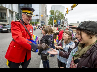 RCMP Chief Superintendent Tony Hamori hands out wristbands during the Calgary Pride Parade in the city's downtown core on Sunday, Sept. 4, 2016. About 60,000 people were expected to watch the annual parade, as more than 125 entries took part. Lyle Aspinall/Postmedia Network