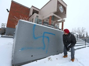Harpeet Singh Gill, a volunteer at the Sikh Society Temple, examines graffitti on the ouside of the building located on 81 St SW on Friday December 23, 2016 in Calgary, Alta. The spray paint was discovered a day or so ago and is similar to both a swastika and a Hindu symbol. Jim Wells//Postmedia