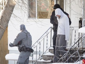 A male is escorted by police out of home on Stanley Rd SW in Calgary, Alta., on Thursday, Jan. 12, 2017. Police arrested a man after a lengthy stand-off following an EMS worker being hurt while responding to a medical call at the home. Lyle Aspinall/Postmedia Network