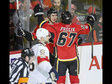 Mikael Backlund and Michael Frolik of the Calgary Flames celebrate Backlund's second of two second-period goals near Jakub Kindl of the Florida Panthers during NHL action in Calgary, Alta., on Tuesday, Jan. 17, 2017. Lyle Aspinall/Postmedia Network