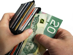 The action of pulling canadian money out of a wallet. ORG XMIT: POS1610071939292809