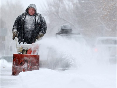 Gerald Elliott acts as a snow angel in the community of Maryland Heights as he clears sidewalks along a block on Sunday February 5, 2017. Snow is forecast continue through Monday and caused collisions across the city.