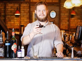 Evan Cooper, a bartender at Cannibale, holds up the Demogorgon Stranger Things inspired cocktail that he dreamed up on January 26, 2017. KERIANNE SPROULE/POSTMEDIA