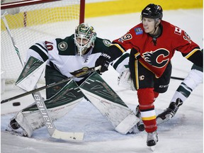 Minnesota Wild goalie Devan Dubnyk hones in on a puck Calgary Flames left winger Matthew Tkachuk tries to deflect in Calgary on Wednesday, Feb. 1, 2017. (The Canadian Press)
