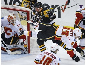Pittsburgh Penguins captain Sidney Crosby collides with Calgary Flames' Sam Bennett in front of Flames goalie Chad Johnson in Pittsburgh on Tuesday, Feb. 7, 2017. (Gene J. Puskar/AP Photo)