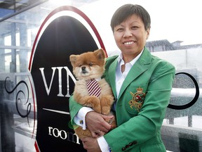 Phoebe Fung, proprietor of Vin Room West in Calgary, is all smiles with her Pomeranian named Dom.