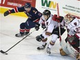 Hitmen defenceman Jake Bean scrambles out of his own end in front of goalie Kyle Dumba and Regina Pats' Jeff de Wit at the Scotiabank Saddledome on Tuesday, March 28, 2017. (Jim Wells)
