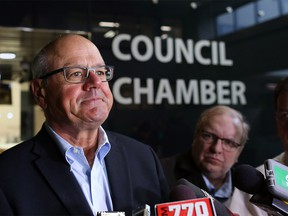 Calgary Flames President and CEO Ken King speaks with the media outside council chambers Monday.