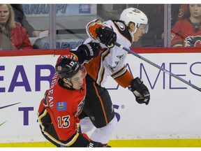 Calgary Flames' Johnny Gaudreau knocked aside by Anaheim Ducks' Hampus Lindholm at the Scotiabank Saddledome in Calgary on Dec. 4, 2016. (Mike Drew)