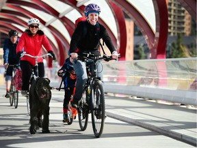 Shelley Cyre and her son Wyatt chug along the Peace Bridge with their dog Midas while family friend Marla Heim follows behind in Calgary, Alta., on April 17, 2017. The Cyre family will be taking some time to see Canada from the road as they take on a four month tour to celebrate Canada 150. Ryan McLeod/Postmedia Network