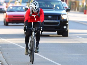 Cyclists ride in the designated bike lane on northbound 10 St and 5 Ave NW in Calgary
