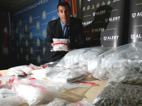 Staff Sgt. Garth Kowalyk with ALERT, poses with some of the drugs seized in Calgary last week.