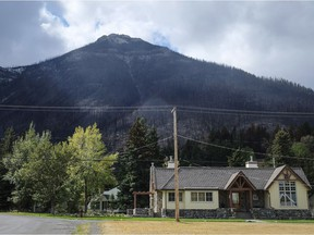 Houses are dwarfed by a burned mountainside in Waterton Lakes, Alta., Wednesday, Sept. 20, 2017. The townsite, which is inside Waterton National Park, was evacuated on Sept. 8 due to the Kenow wildfire.THE CANADIAN PRESS/Jeff McIntosh ORG XMIT: JMC108 Jeff McIntosh,