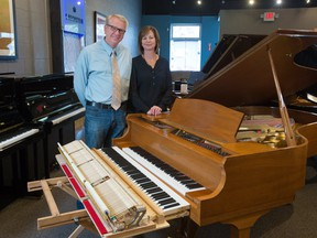 Michael and Nicole Lipnicki, of Michael Lipnicki Fine Pianos, stand next to the keyboard of a 7/8 piano with a regular keyboard next it for scale in the store on Tuesday October 31, 2017. The piano's keyboard was modified for a customer in Calgary and is the first one in the city. Gavin Young/Postmedia
