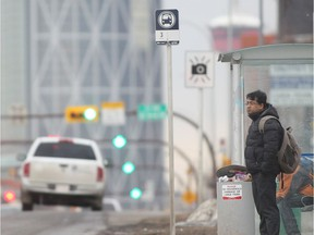 A passenger waits for a downtown bus on Centre Street at 22nd Avenue NW in this file photo from Feb.18, 2015.