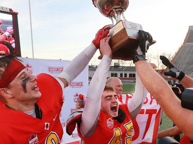 U of C Dinos kicker Niko Difonte raises the Hardy Cup after his 59 yard field goal in the final seconds cinched the game over the UBC Thunderbirds 44-43.