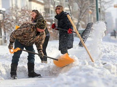 Patrick Boyle and Kara, left and Vesna Turk teamed up to clean their sidewalk in Kensington Wednesday December 20, 2017. An overnight winter storm hit Calgary leaving over 20 centimetres in parts of the city.