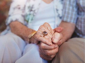 Cropped shot of elderly couple holding hands while sitting together at home. Focus on hands. Getty Images/iStockphoto