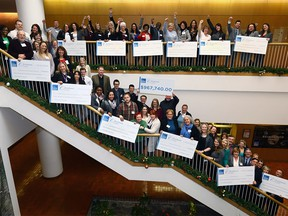 Represenatives from 12 charities with staff hold up their cheques distributed at the Calgary Herlad building from this years $967,740.00 raised from the Calgary Herald Christmas Fund on Wednesday February 7, 2018. Darren Makowichuk/Postmedia