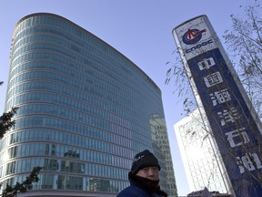 A man walks past the headquarters of the state-owned China National Offshore Oil Corp. (CNOOC) in Beijing.