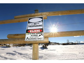 A warning sign is posted on a fence at the entrance to a rural property north of Okotoks, Alberta, south of Calgary on Tuesday, February 27, 2018. Jim Wells/Postmedia