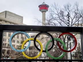 The Calgary Tower is seen with Olympic rings built into railing at Olympic Plaza in downtown Calgary, Alta., on Monday, March 20, 2017. The city is considering another Winter Olympics bid. Lyle Aspinall/Postmedia Network