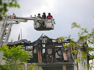 Fire investigators examine an early morning four alarm fire which caused extensive damage to a condo complex in Inglewood on Wednesday May 30, 2018.