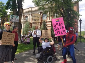 People hold signs outside of a courthouse in Medicine Hat, Alta. on Wednesday, June 20, 2018. A big crowd showed up this morning for the first court challenge to an Alberta law barring schools from telling parents if their children join a gay-straight alliance. A Court of Queen's Bench justice in Medicine Hat is hearing an application from faith-based schools and parents to halt the legislation until there's a ruling on its constitutionality.