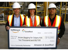 Jeff Hyde, Senior VP Development at QuadReal Property Group, Tanya Koshowski, Executive Director at Brown Bagging For Calgary's Kids and Vibhore Arora, Director of Regional Operations at Amazon hold a cheque for $10,000 that was presented at the new Amazon Fulfillment Centre still under construction in Rockyview County just outside of Calgary. Tuesday, June 12, 2018. Dean Pilling/Postmedia