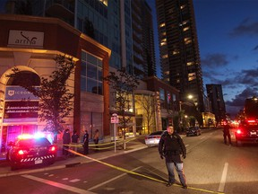 Calgary police direct traffic after severe winds tore out windows in an apartment building at 11 ave and 3st s.e. in Calgary, Ab., on Friday July 13, 2018. Mike Drew/Postmedia