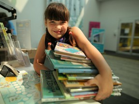 Adelaide Longfield, 7, checks out a stack of books at Nose Hill Library in Calgary, on Thursday August 16, 2018 in advance of Saturday's Calgary Public Library's event Love Your Library Day. Leah Hennel/Postmedia
