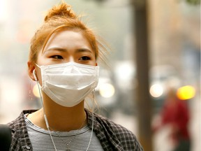 Eojin Kim covers up while walking in smoky downtown Calgary on Wednesday Aug. 15, 2018.