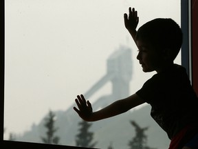 Andres Cortes peers out the window on Thursday, Aug. 16, 2018, at Canada Olympic Park's Winsport, where he is attending a soccer camp. Winsport has had to keep kids busy with indoor activities as smoke from B.C. wildfires settles over Calgary.