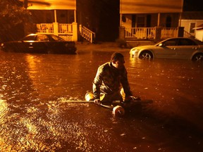 Michael Nelson floats in a boat made from a metal tub and fishing floats after the Neuse River went over its banks and flooded his street during Hurricane Florence September 13, 2018 in New Bern, North Carolina. C