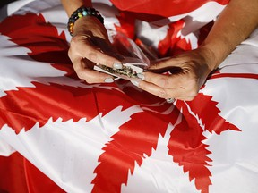 A cannabis user rolls a joint at a rally in Calgary after the legalization of cannabis on Oct. 17, 2018.